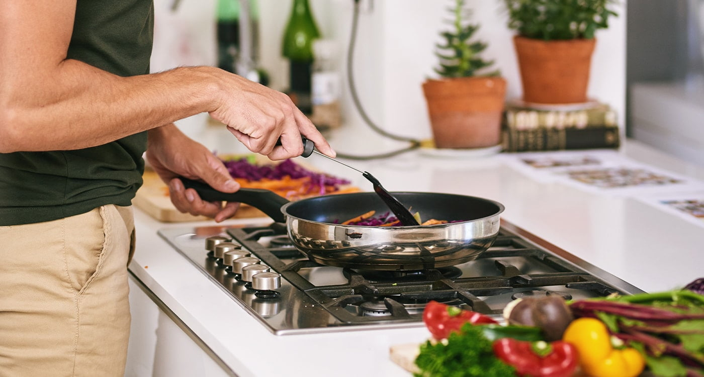 person cooking vegetables in a pan on the stove