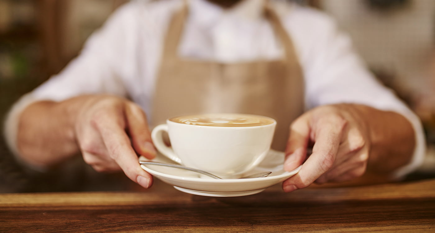 hands holding a coffee cup on a saucer