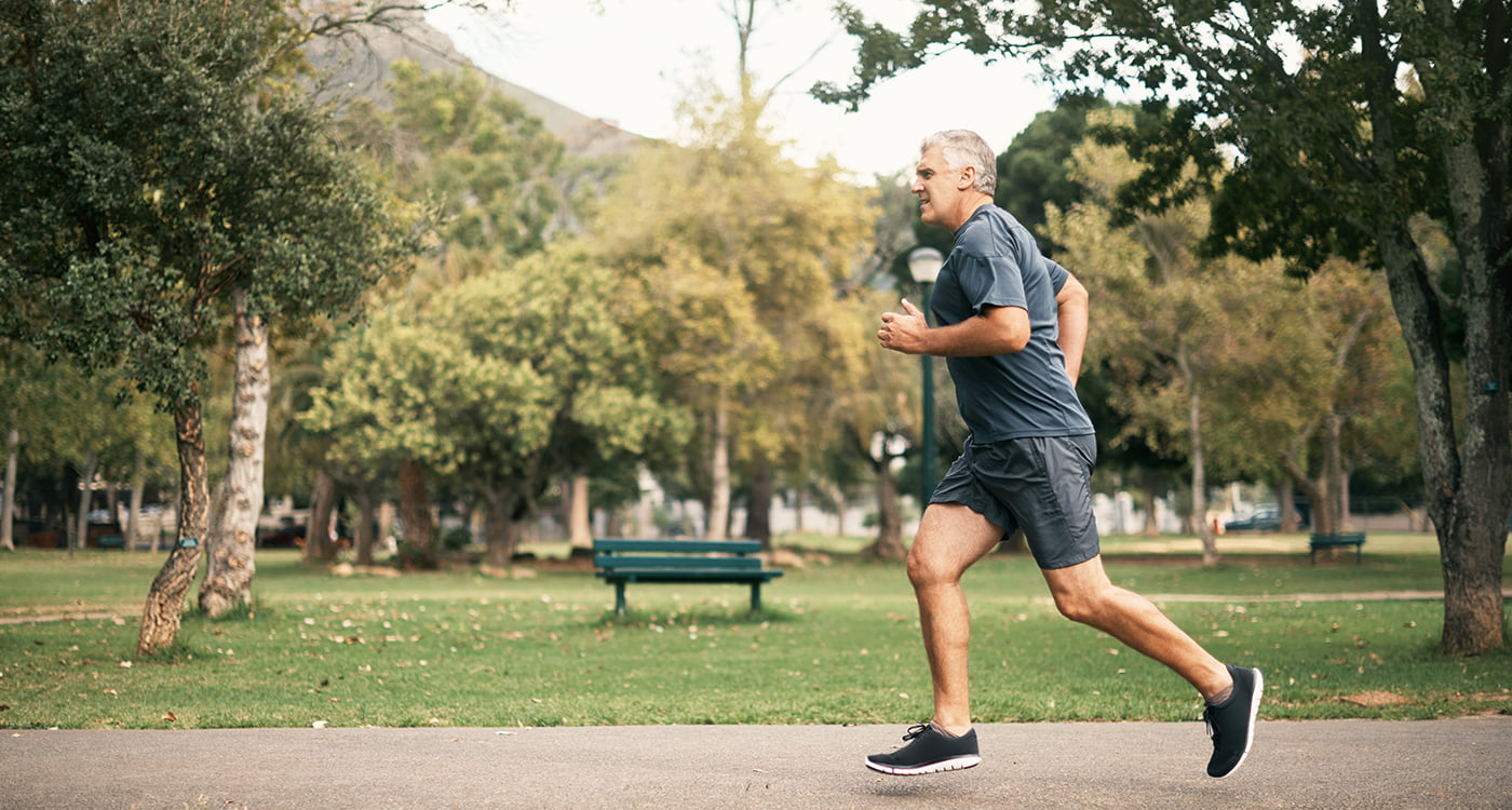 an older man running in a park